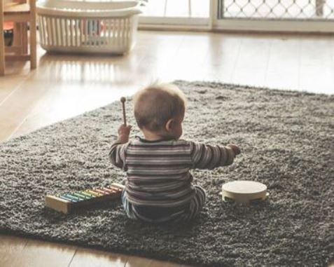 Infant sits on carpet playing xylophone at childcare of southwest Florida